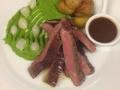 Steak z hovězího pupku připravený metodou sous vide s hráškovým purée, cibulkami, pečenými brambůrkami Grenaille a pepřovou omáčkou